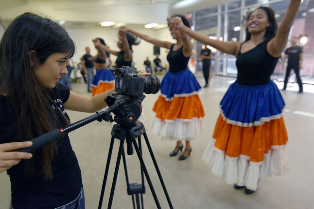 Woman videotaping women dancing in blue and orange skirts