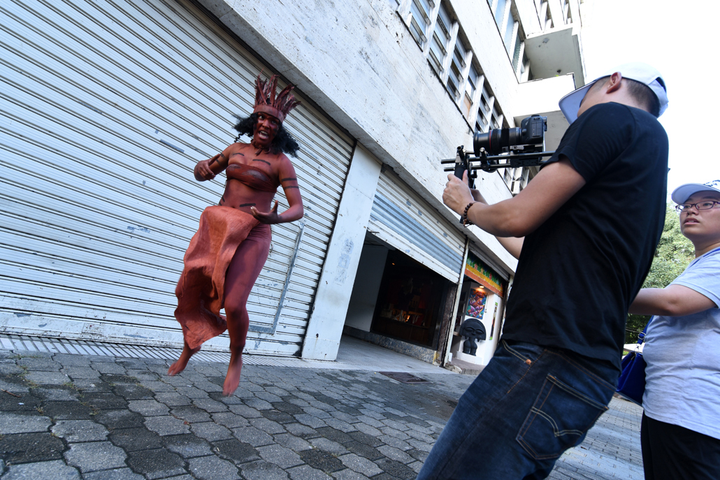 Man filming a woman in tribal clothing and body paint on the street
