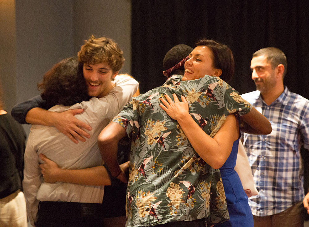 group of people hugging at the 2016 nyfa fall film commencement ceremony