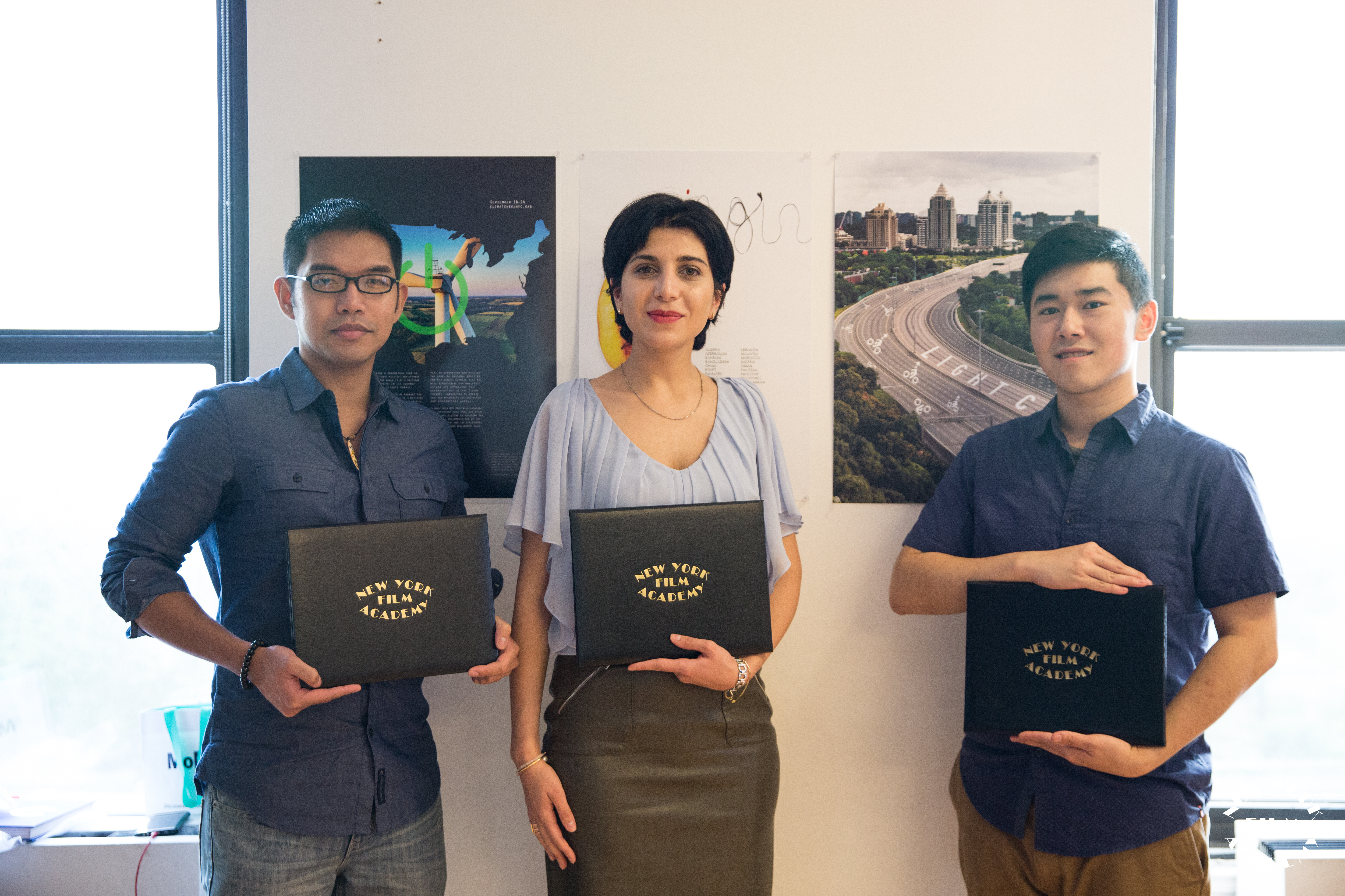 3 students holding NYFA graduation folders