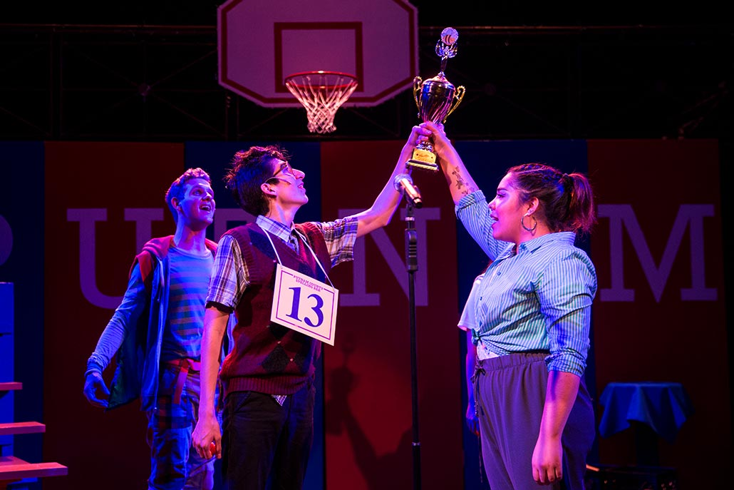NYFA musical theatre students hold large trophy up high in Spelling Bee.
