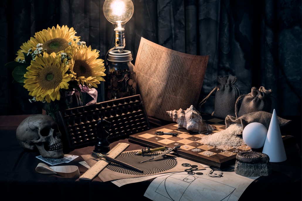 Desk with drawings, chess board, flowers, light and skull