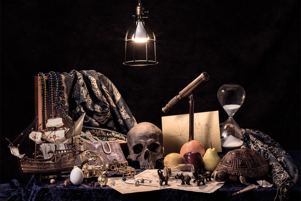 Ship, hourglass, skull, fruit, and turtle arranged on desk with light overhead