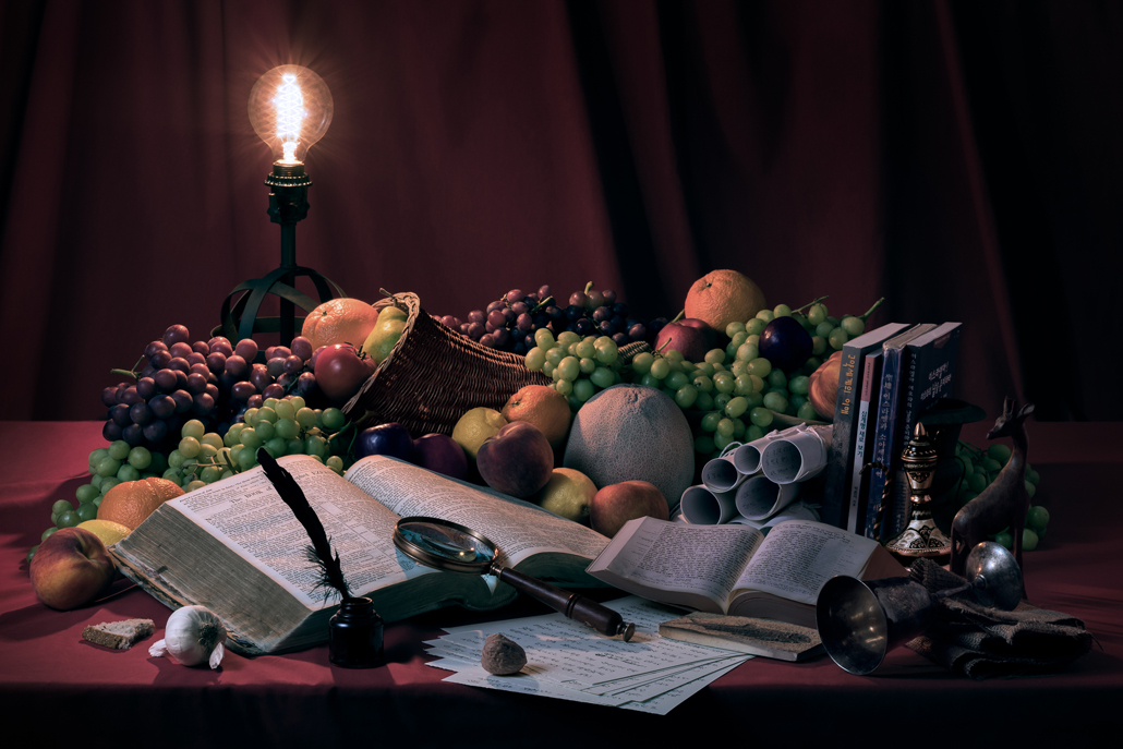 Still life photograph of books, fruit, and a light arranged on a desk