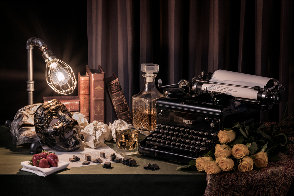 Still life photograph of typewriter, masks, flowers, and books on a desk