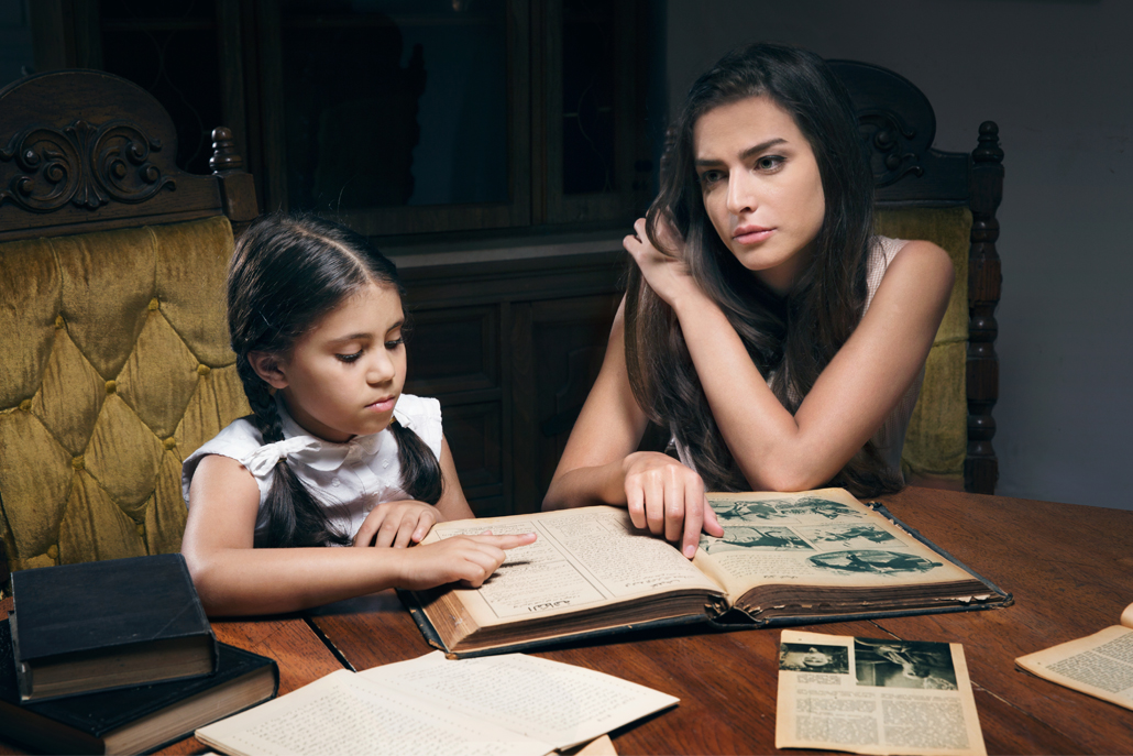 Mother and daughter sitting at table looking at old newpaper clippings and pictures