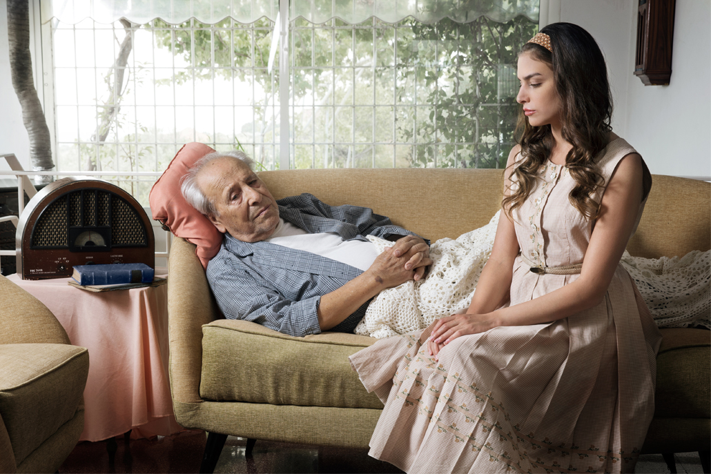 Woman sitting next to elderly man laying on couch