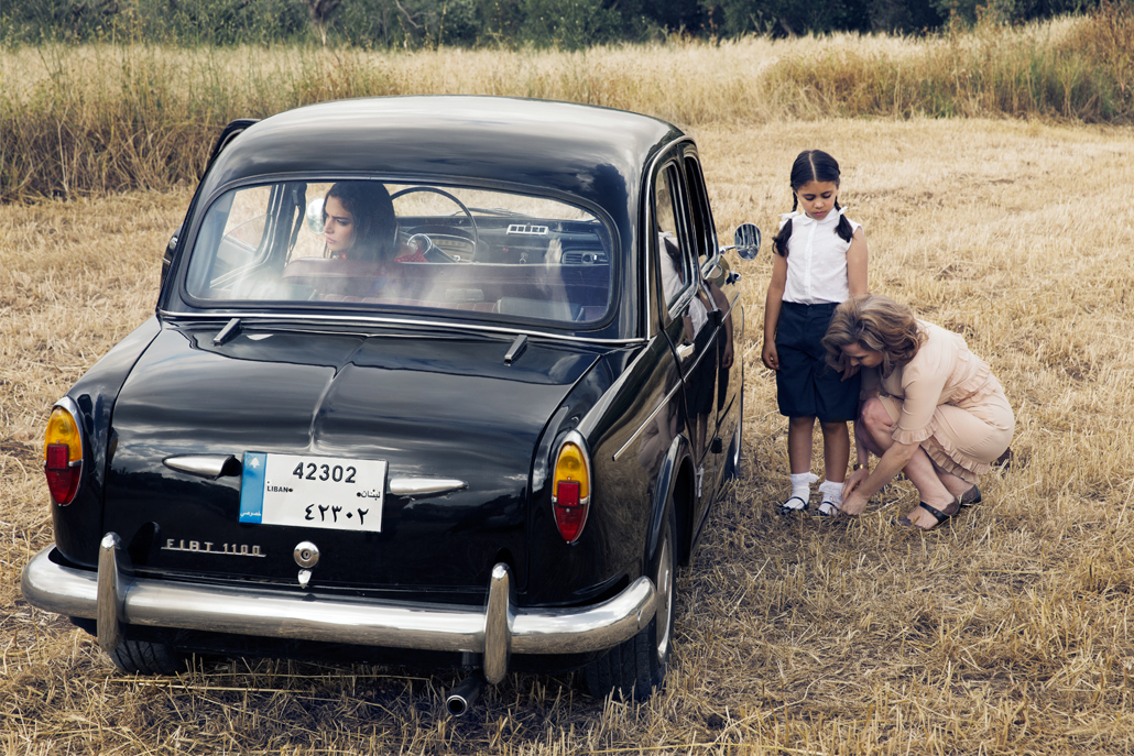 Woman fixing girl's sock in field with old car parked next to them