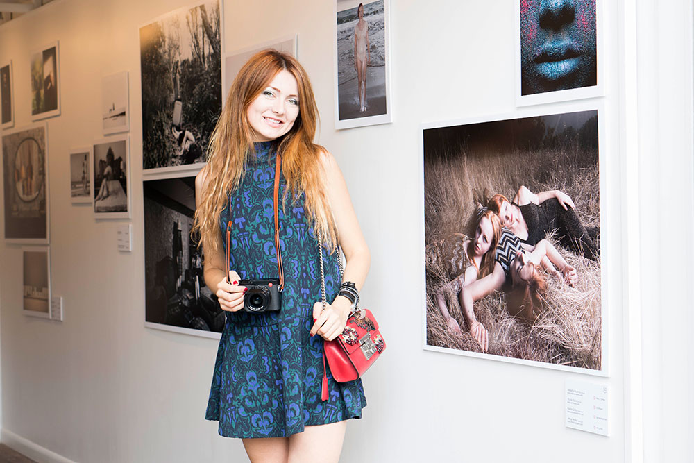 Woman posing with camera in front of photo exhibit