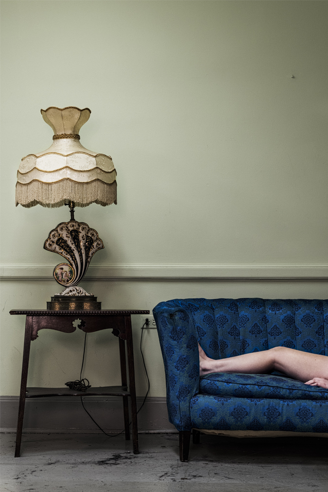 Legs laying on blue couch next to side table with ornate lamp