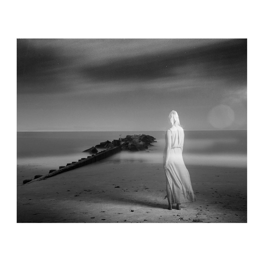 Transparent woman standing on shoreline of foggy island