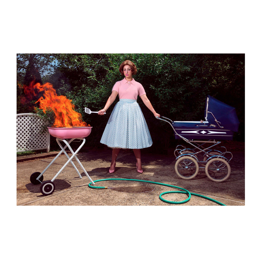 Woman pushing stroller and cooking with grill that is on fire