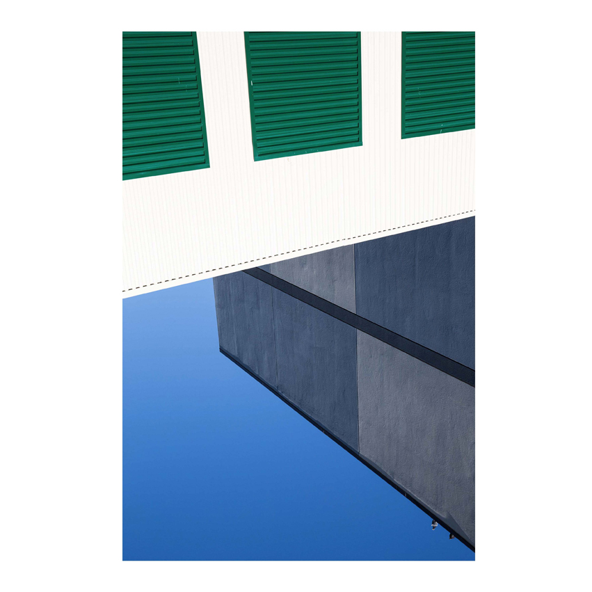 White wall with green shutters and photo of building and sky below it