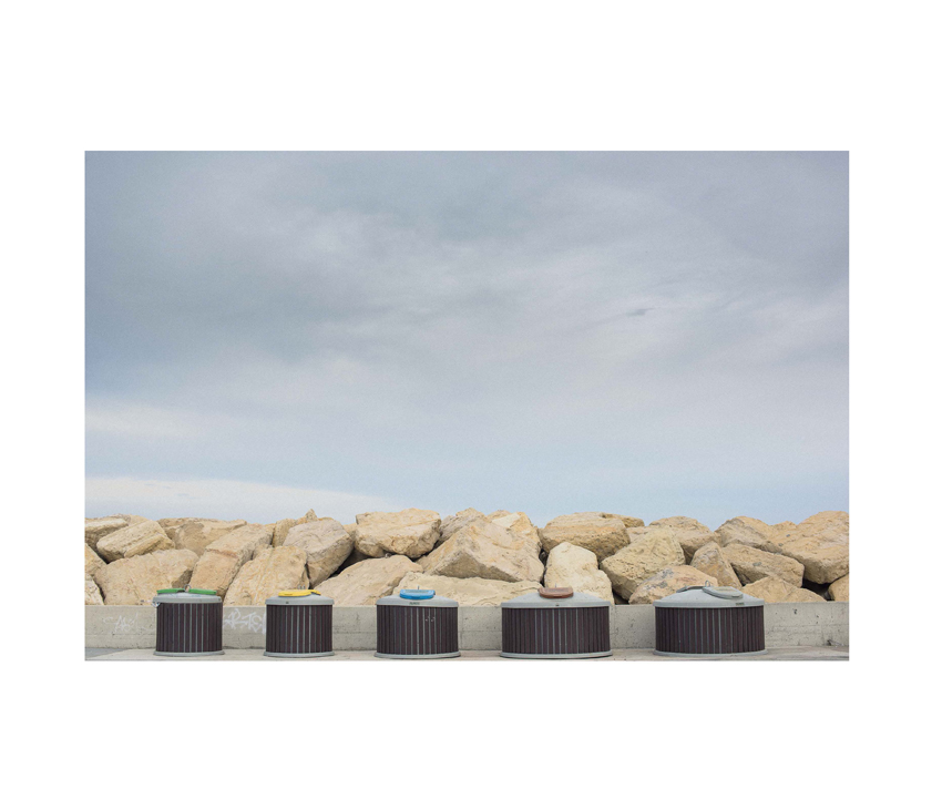Five roof air vents with rocks and sky in background