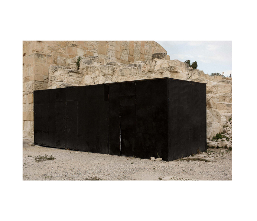 Large black rectangular box sitting in front of rocky hills