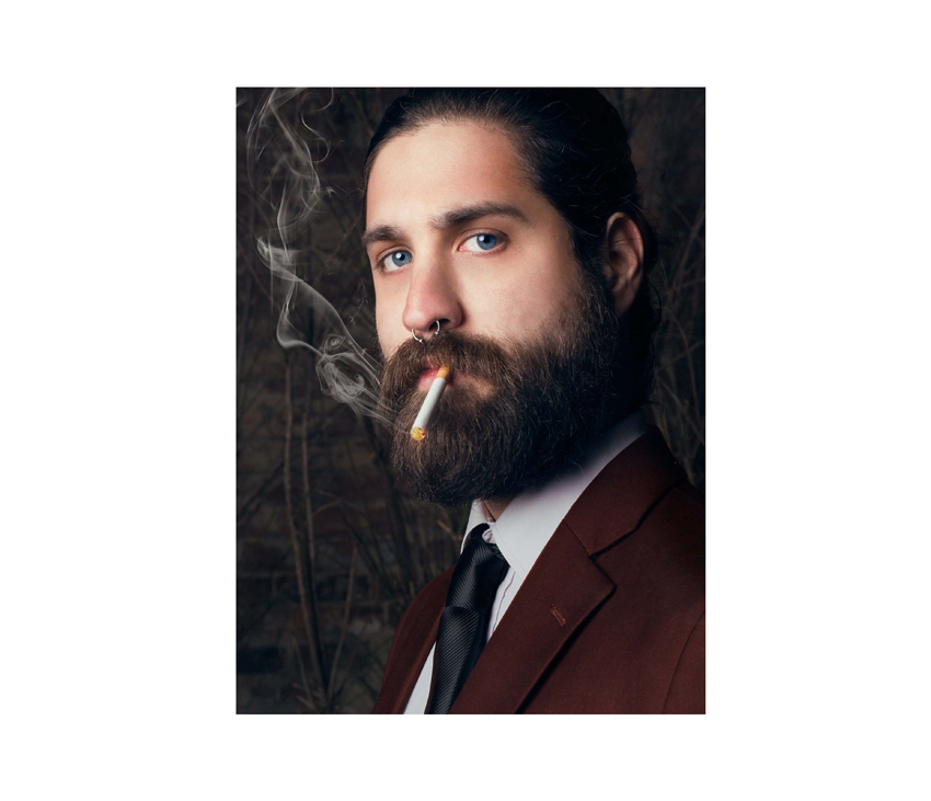 Man posing with beard and long hair smoking a cigarette in a suit