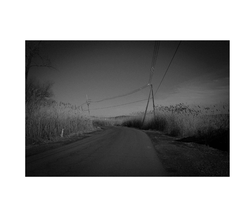 Black and white photo of rural road with telephone poles