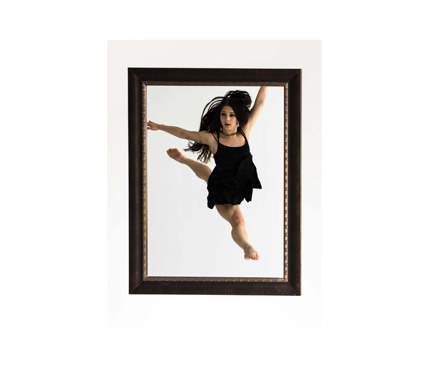 Woman in black dress dancing within black photo frame