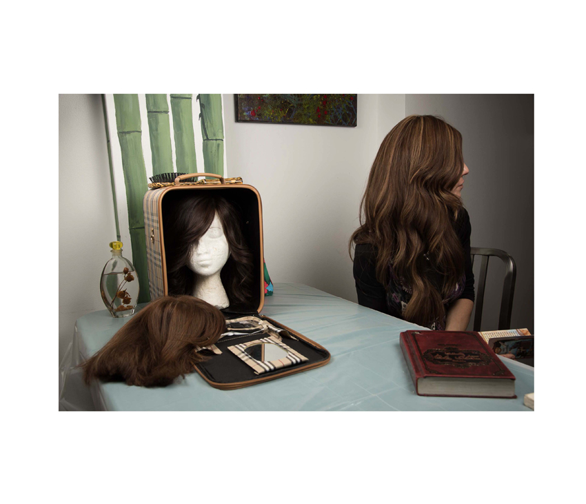 Woman sitting with bag of wigs on top of table