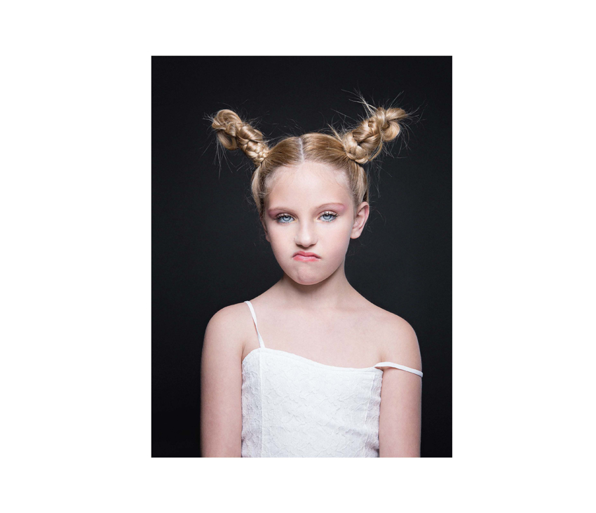 Girl with hair in buns frowning at camera