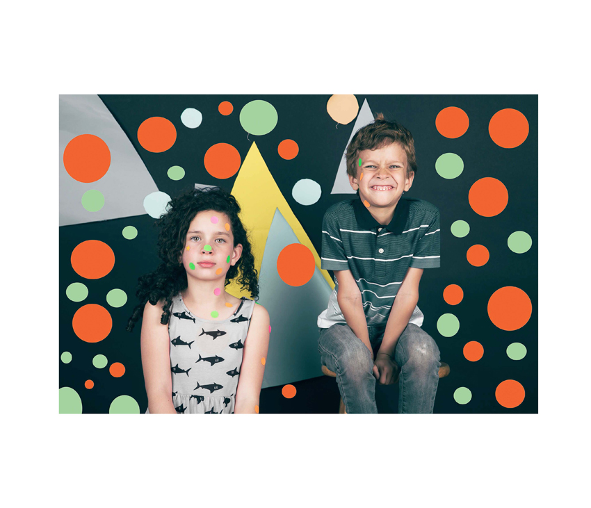 Two kids posing in front of polka dot wall with polka dots on bodies