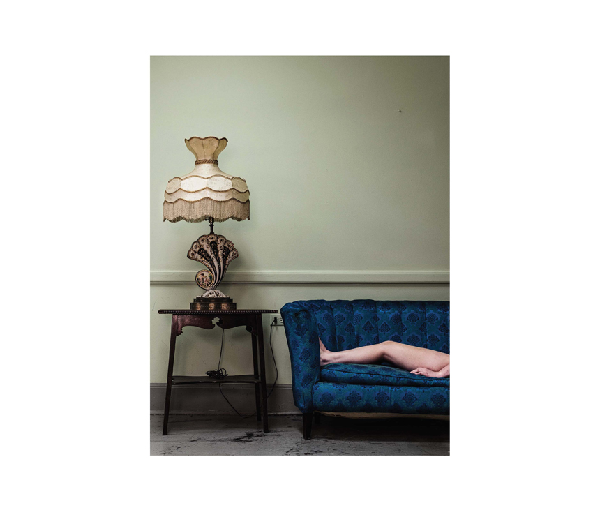 Naked legs laying on blue couch next to shell-shaped lamp