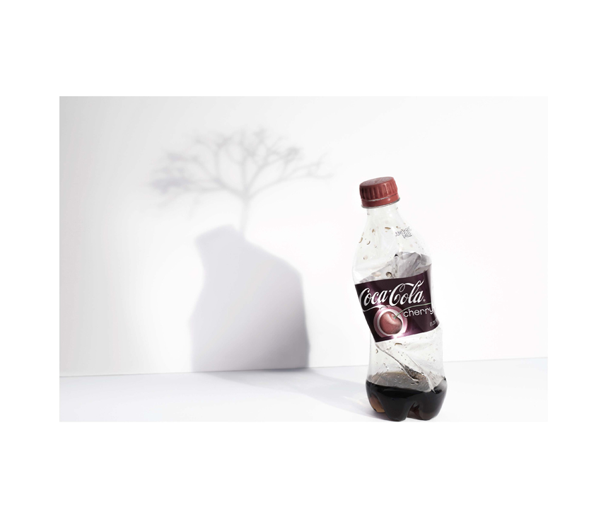 Crushed Coca-Cola Cherry bottle with shadow showing tree growing out of it