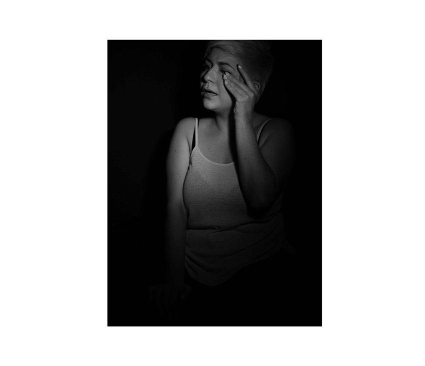 Girl wiping face while crying in front of black background