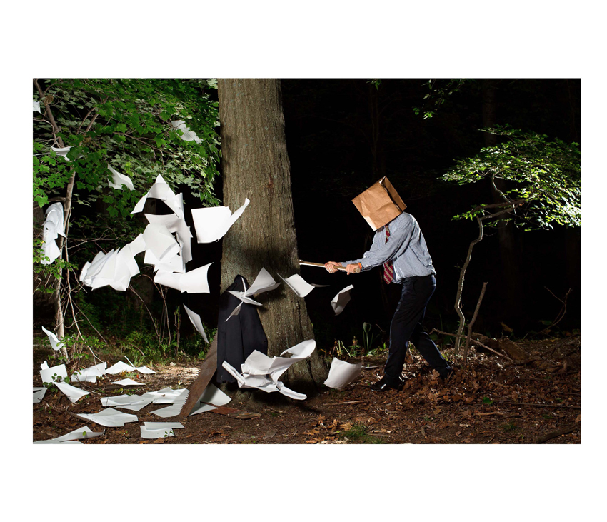 Man with paper bag over head chops down tree with papers flying around