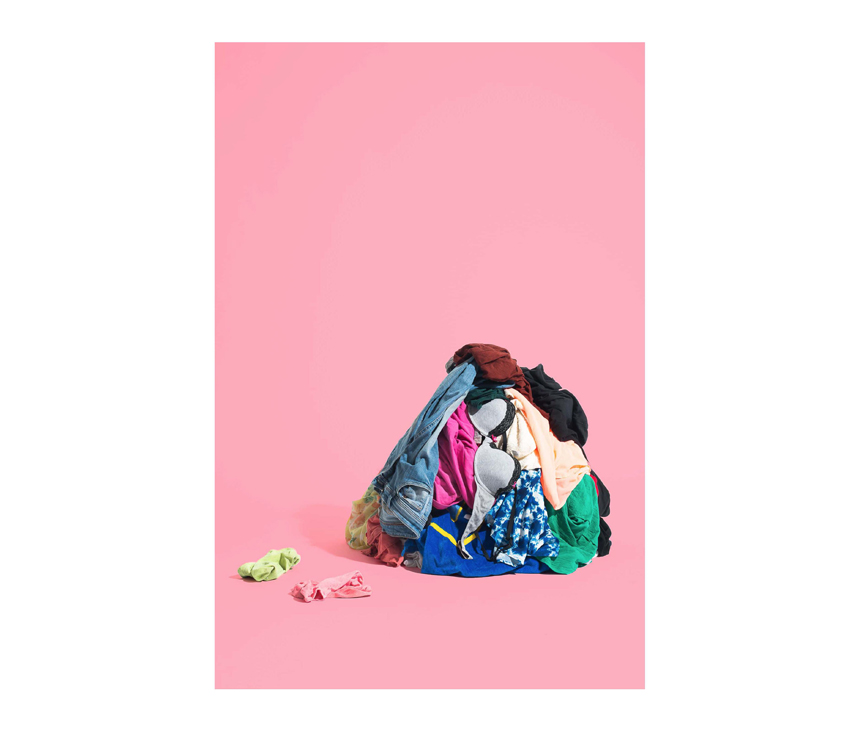 Pile of clothes laying in front of pink background