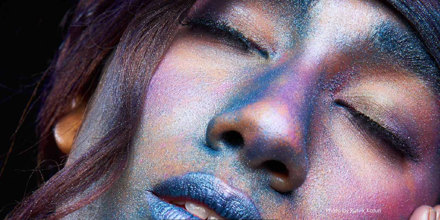 Upclose face of model covered with blue and purple glitter