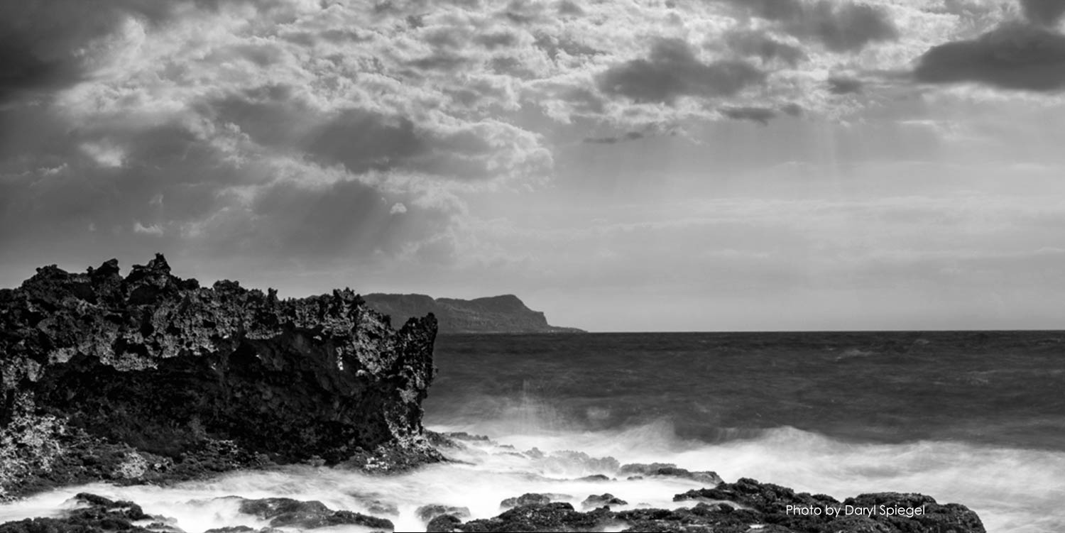 Black and white photo of ocean with rocky shore