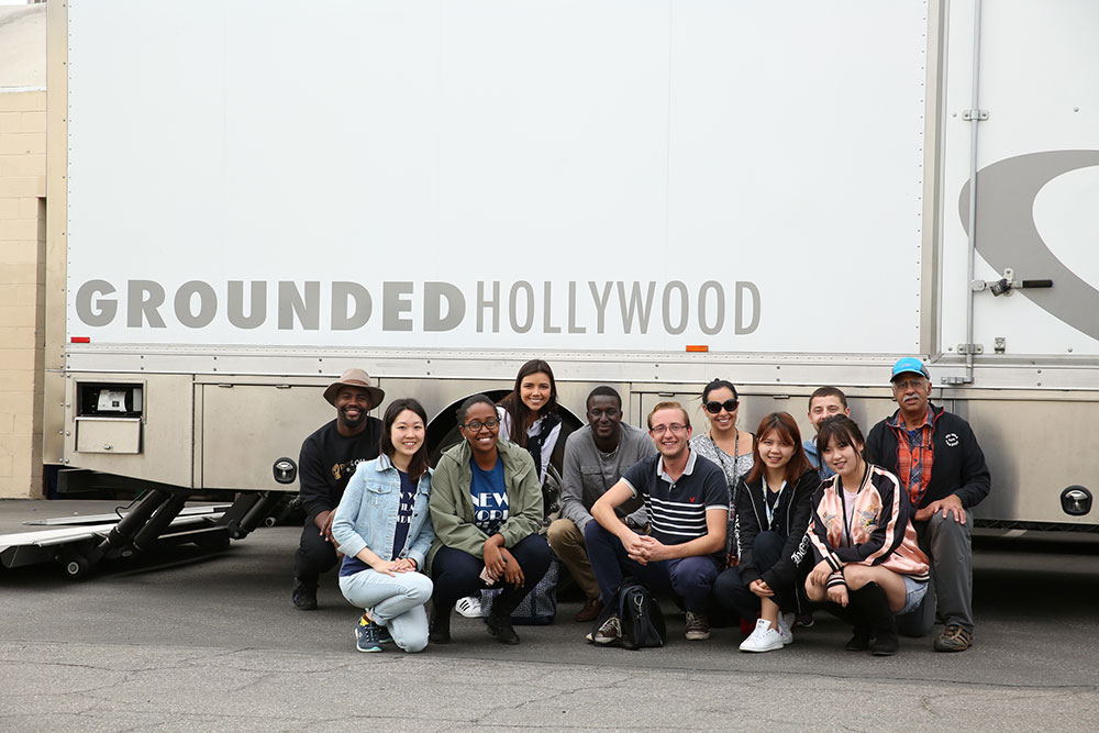 NYFA acting class posing for a group photo in front of a Grounded Hollywood trailer.