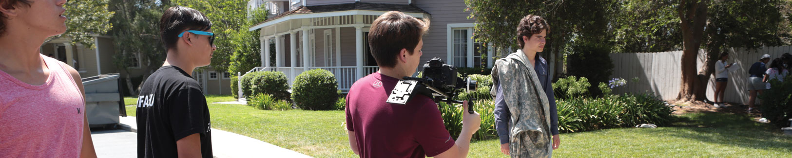 NYFA teen filmmakers shoot a scene with a student actor on the lawn of a large beige house.