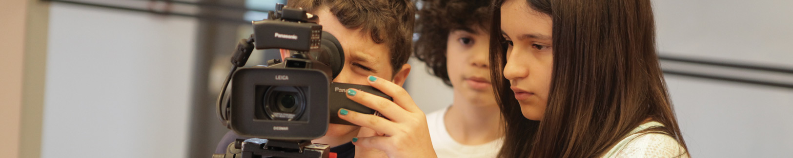 A NYFA filmmaking camp student holds the camera while her classmate peers through the viewer.