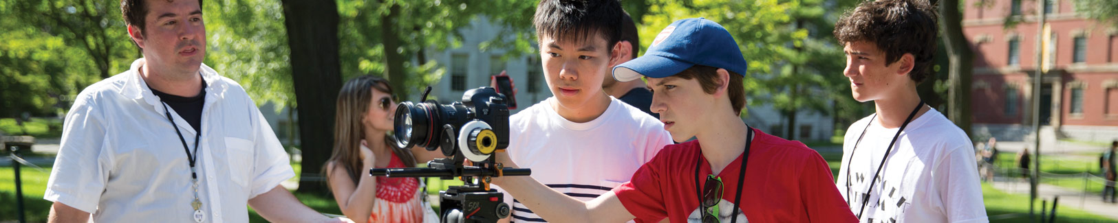 NYFA instructor supervises as his filmmaking students set up their camera outside under green trees.